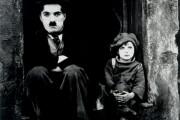 Chaplins pojke - svartvitt fotografi utav Chaplin och pojke i keps.