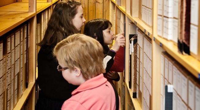 Fotografi utav barn på besök i arkivet. De står mellan arkivhyllorna och läser.