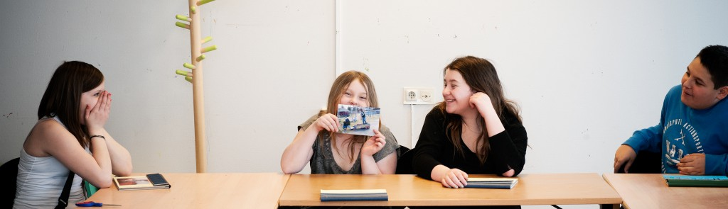 Foto: Krister Hägglund Bild på tre flickor som skrattar. En håller upp ett fotografi.