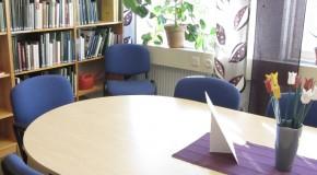 Fotografi från Forskarsal o bibliotek i Umeå. Bord och stolar i förgrunden, bokyllor i bakgrunden.