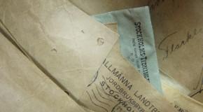 Fotografi utav äldre arkivhandlingar (kuvert i beige och ljusblått)