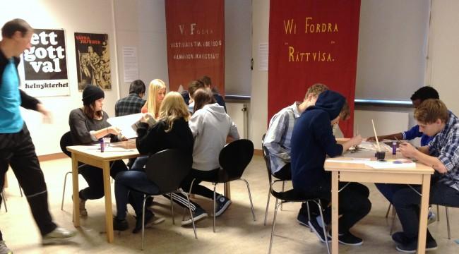 """Fotografi utav ungdomar som sitter vid två bord och arbetar. I bakgrunden röda fanor där det står bland annat """"Wi fordra rättvisa"""""""