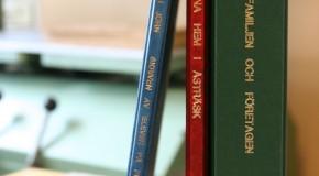 Bild på bokryggar i blått rött och grönt med text i guld präglad på ryggarna