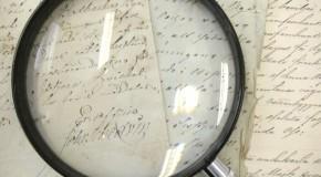 Fotografi utav förstoringsglas som ligger på äldre handskrivna handlingar