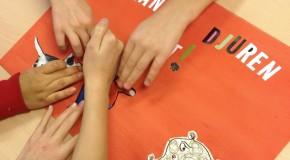 Bild utav barnhänder, de håller på att göra en egen affisch