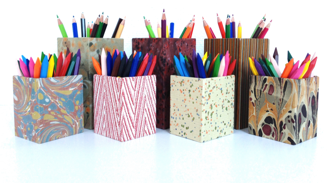 Bild utav sex stycken pennställ eller lådor i olika papper och mönster, fyllda med kritor och färgpennor i alla nyanser.