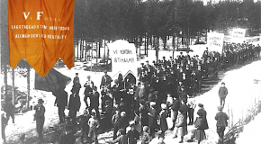 Svartvit äldre bild utav demonstrationståg. I förgrunden syns en fana, den är kolorerad (i rött)
