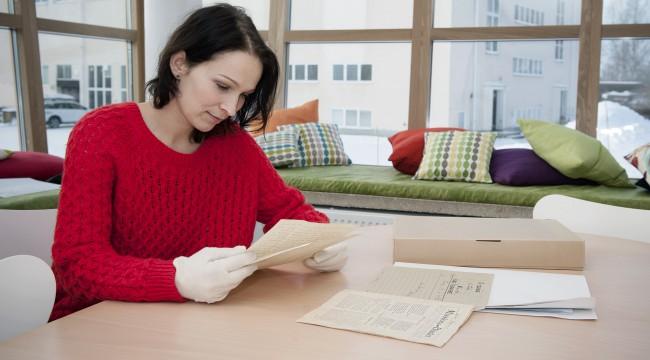 Bild utav kvinna i röd tröja som sitter vid ett bord på Forskarrum Nordanå och läser handlingar. Hon bär bomullsvantar.