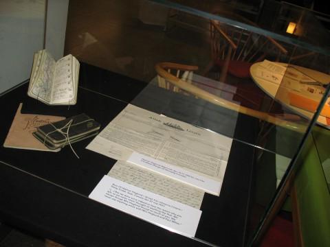 Fotografi på monter med handlingar ur Hjalmar Höglunds arkiv (Almanackor, biljett och brev)