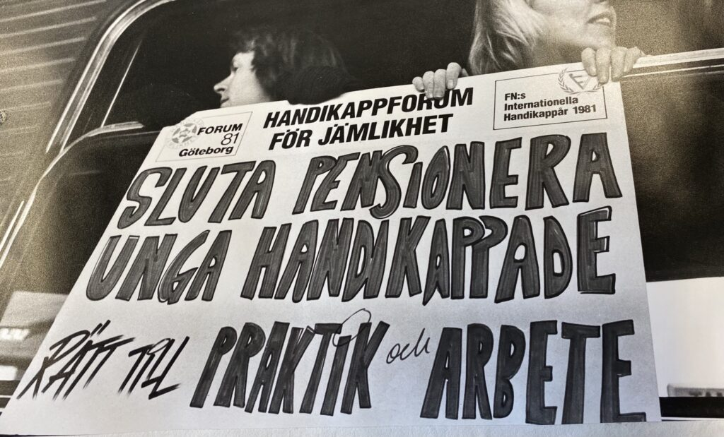 """Tågresenärer med affisch utanför fönstret """"sluta pensionera unga handikappade, rätt till praktik och arbete"""""""